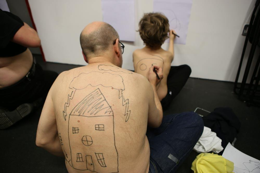 A shirtless man with a drawing of a house on his back draws on a child's back. The child draws on a paper on the wall. Playing Up Test Day.