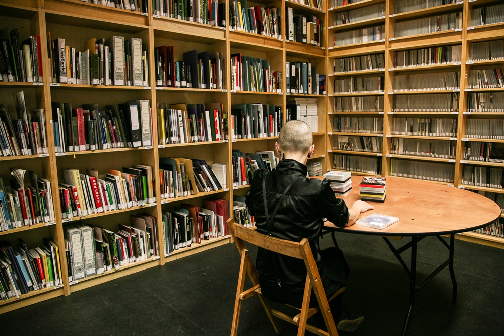 Individual sitting at a table in front of full bookshelves in the study room