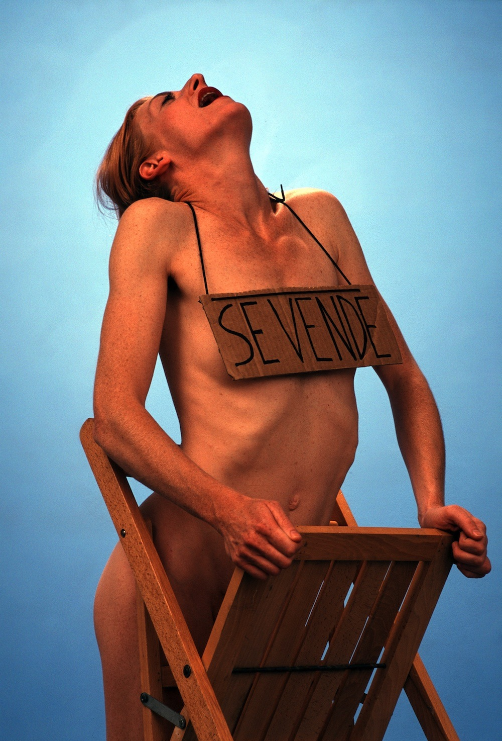 The artist, nude, dances with a chair wearing a sign around her neck that reads 'sevende'.