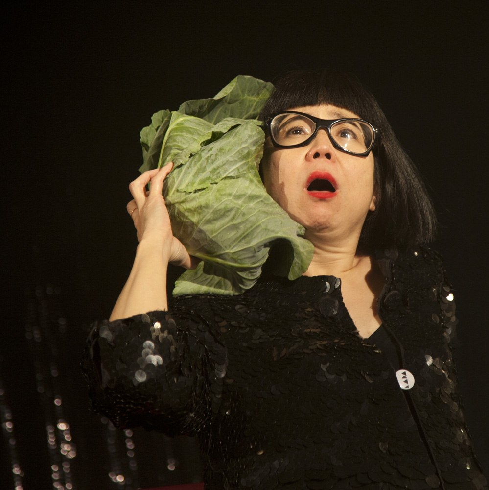 Stacy Makishi in front of a black background, holding a lettuce head next to her head