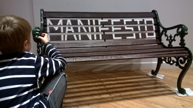 A wooden bench with the word MANIFESTO written on it.