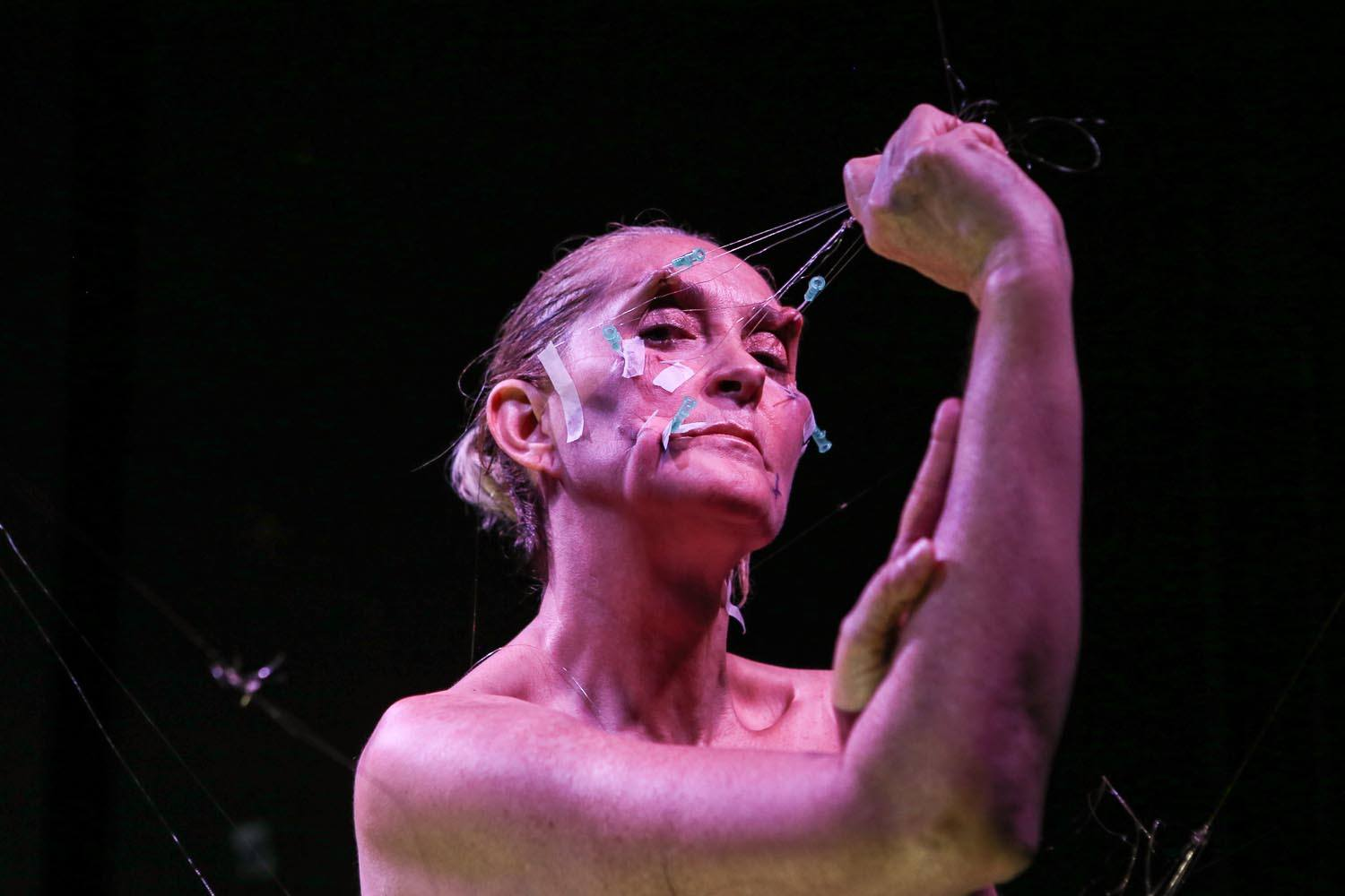 The artist pulls on wire attached to hooked needles in her face, stretching the skin.