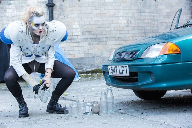 Artist wearing makeup and an American Football plate crouches next to a car.