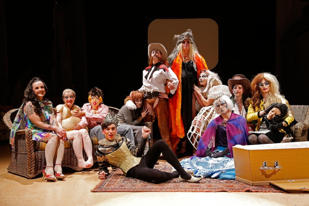 Group of people dressed in drag sitting, standing and lying on the floor