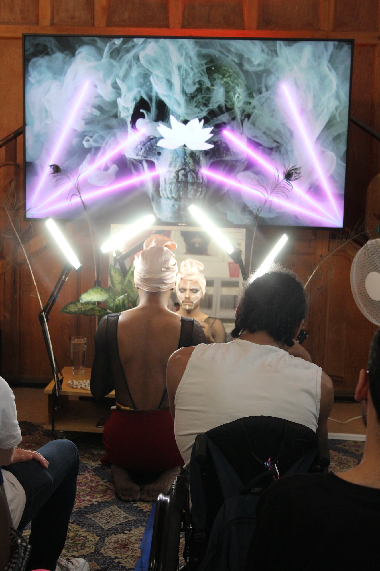 The artist applies their ritualistic makeup in front of a video.
