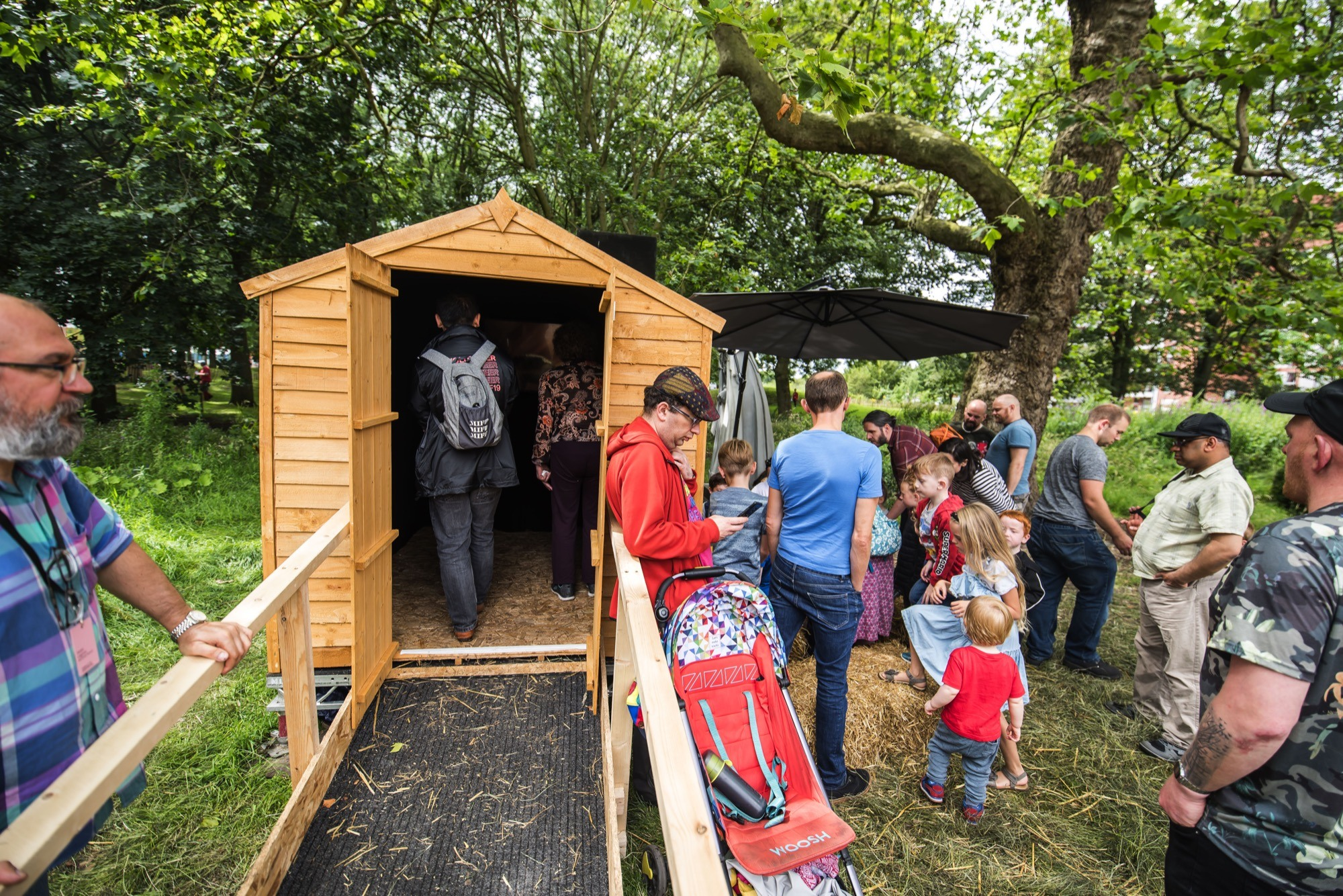 people waiting outside a wooden shed