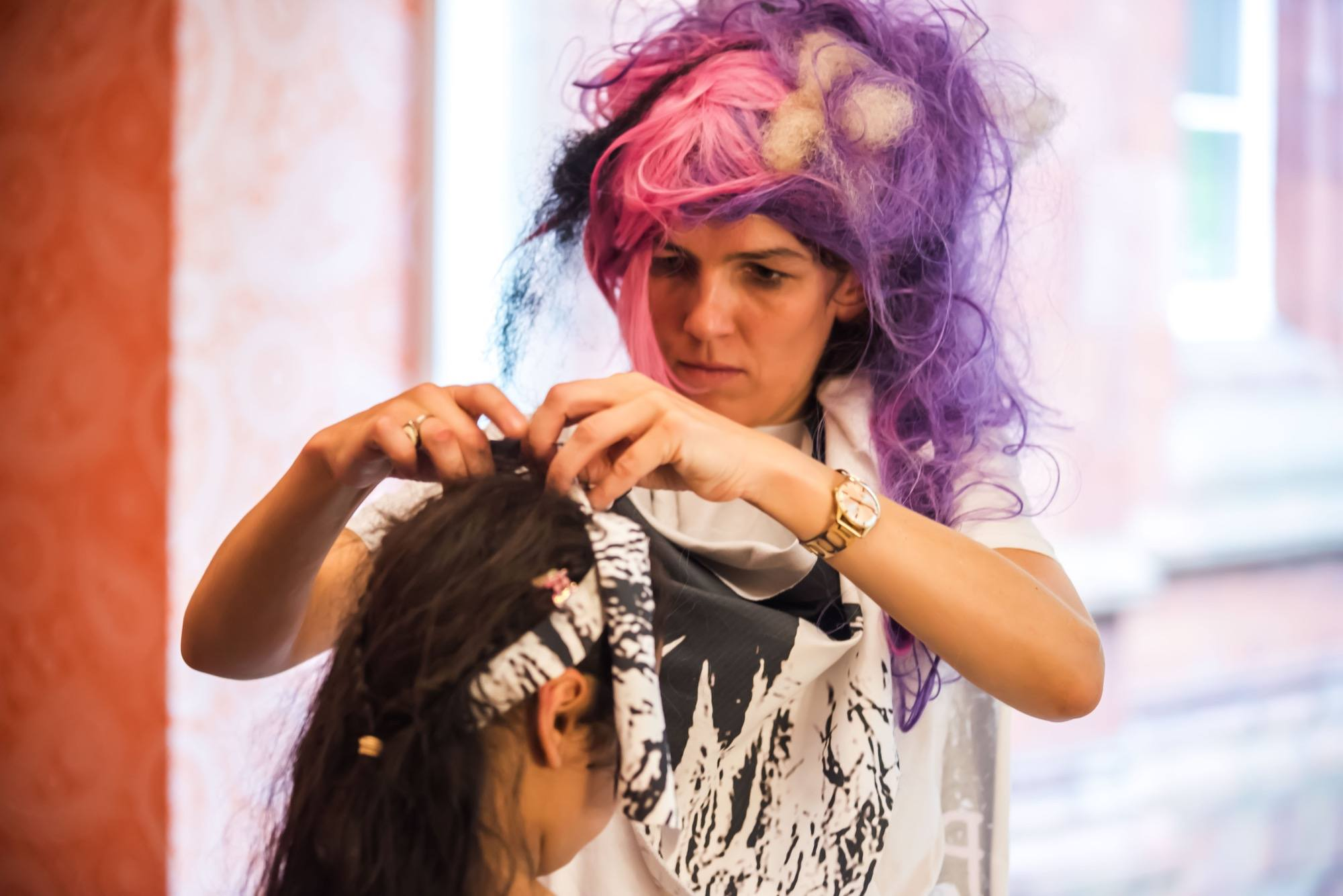 person having their hair done by a woman with crazy pink hair