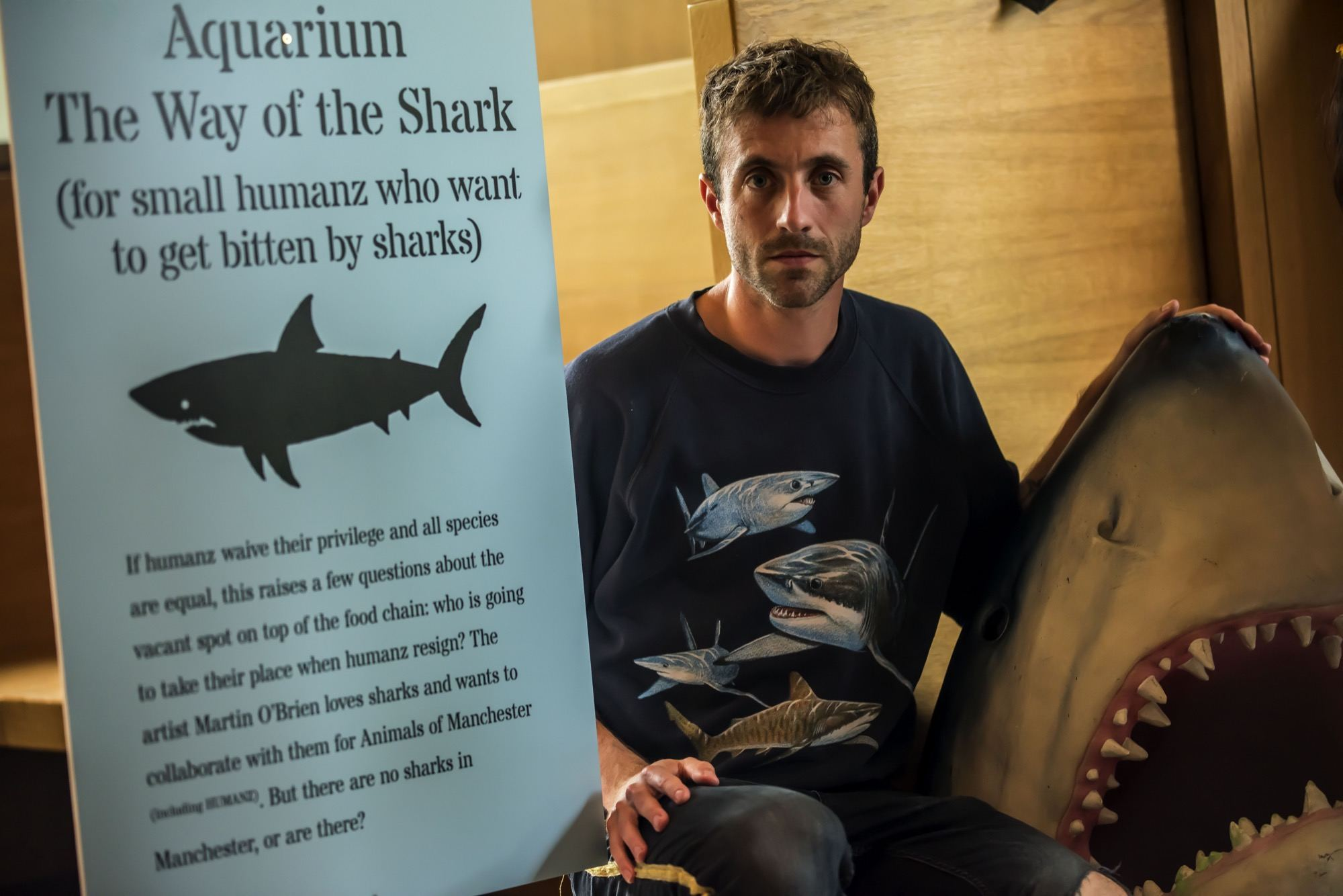 artist martin o brien next to a poster with a shark
