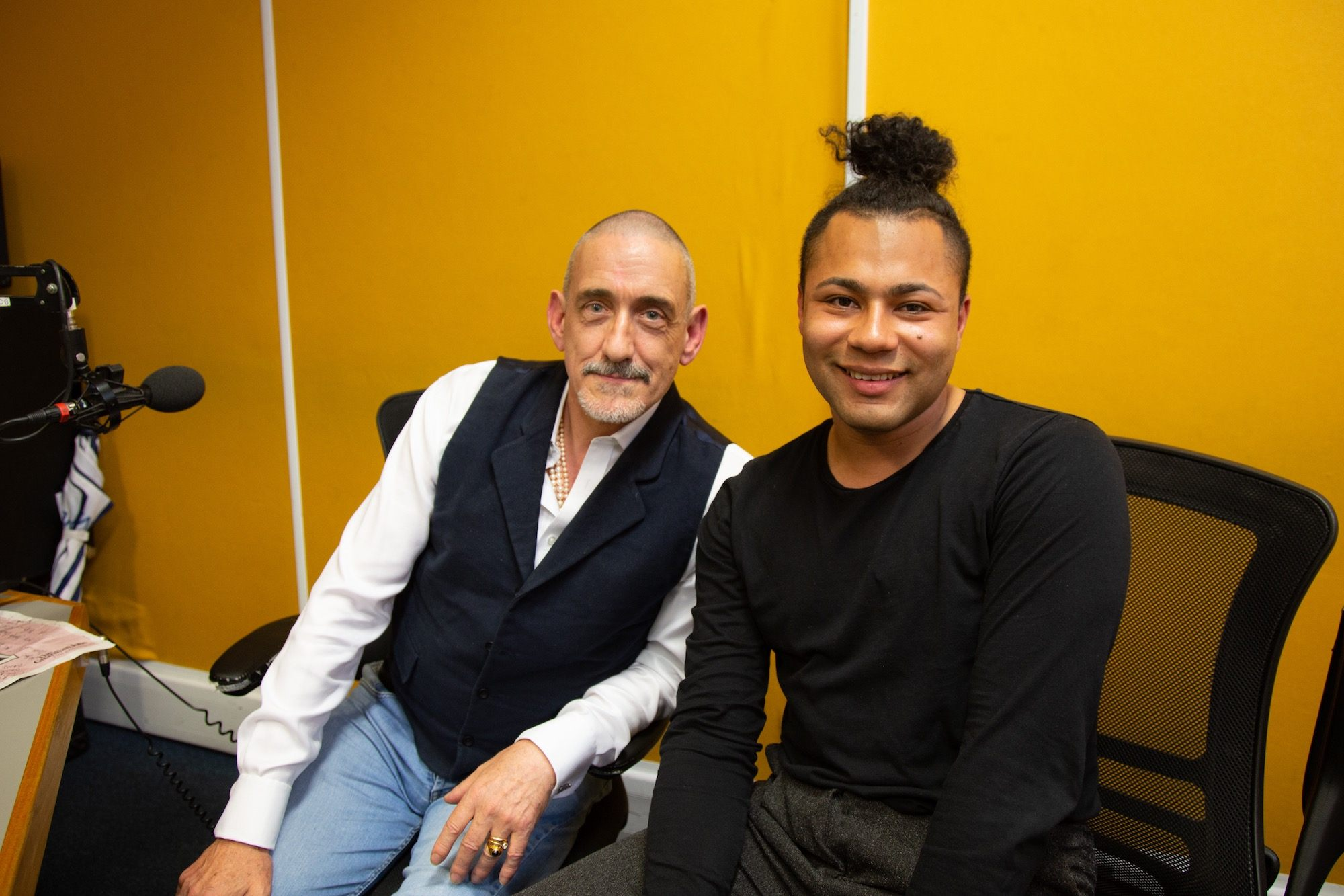 Travis Alabanza and Neil Bartlett sit beside each other in a radio recording studio