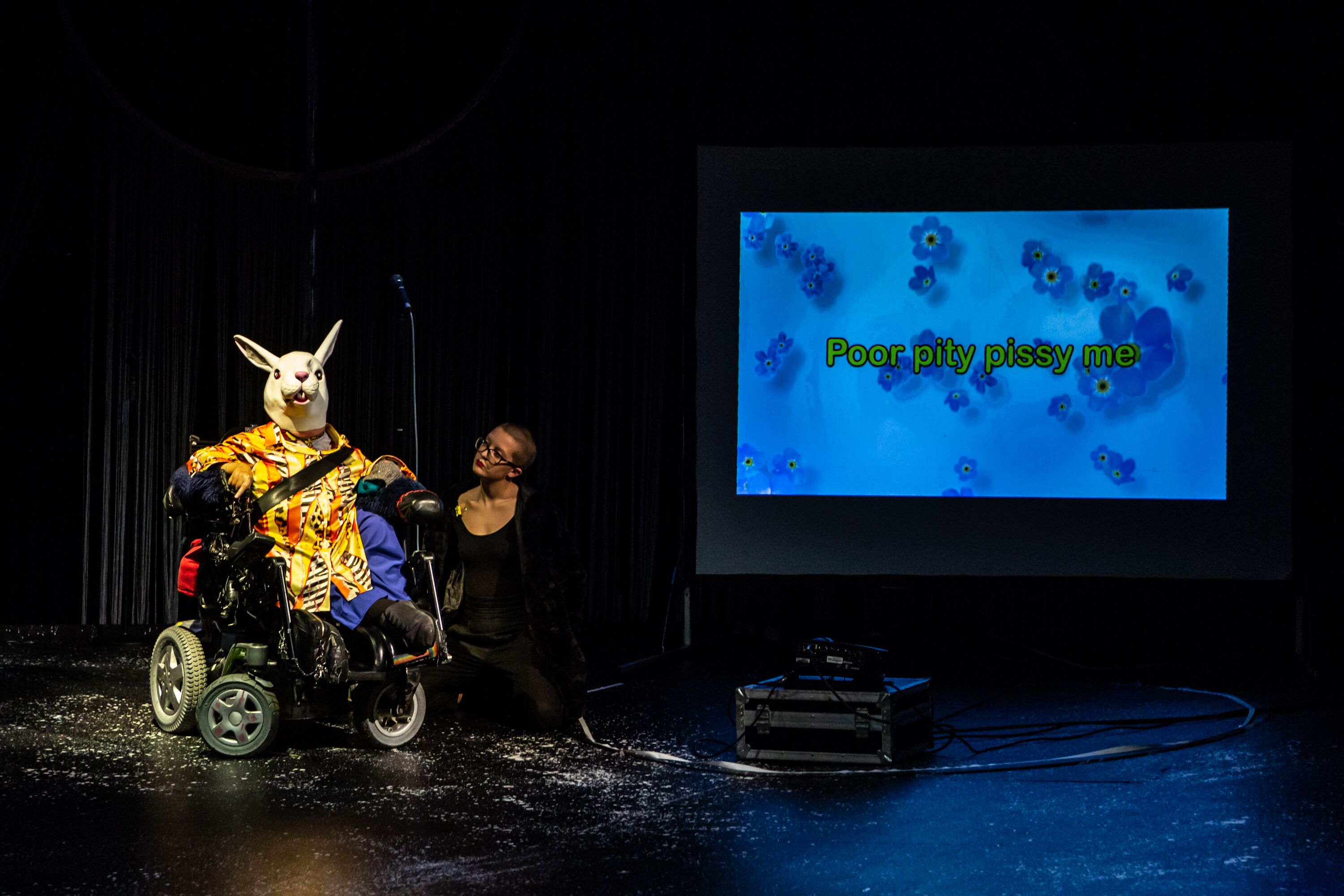 The artist is in a wheelchair and wearing a rabbit mask. To her side is her assistant. There is a screen to the right with the words 'poor pitty pissy me' projected.