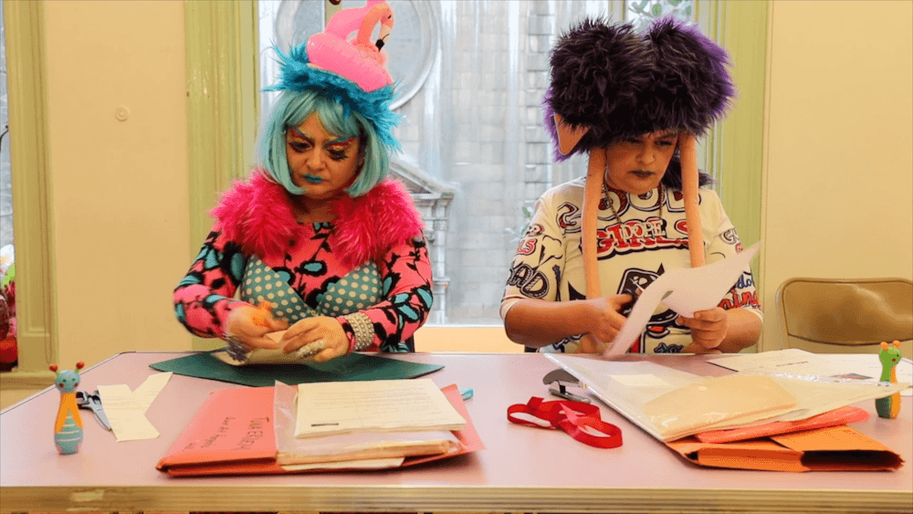 The artists wear fabulous wigs and costumes. They are tearing and cutting strips of paper documents.