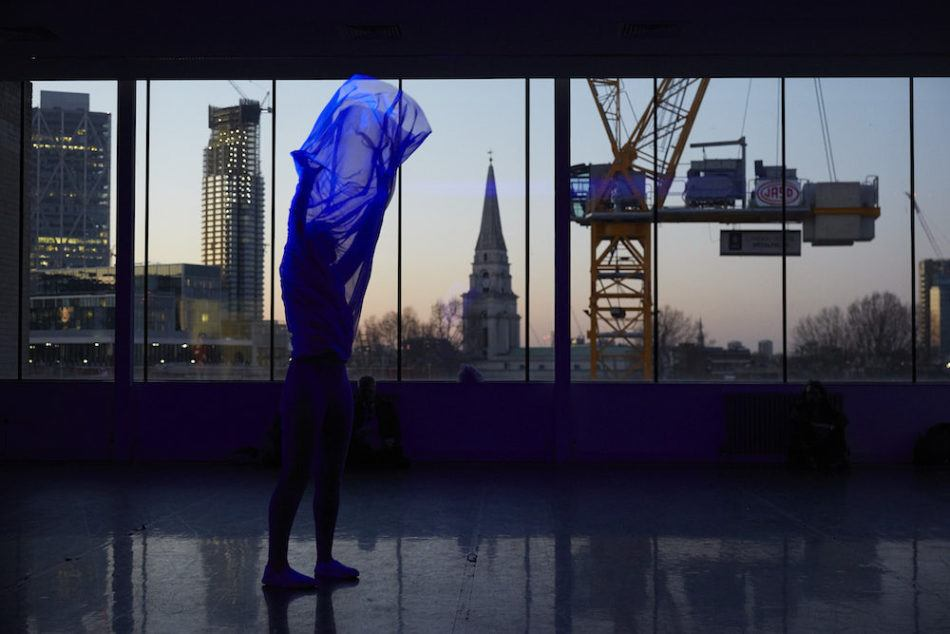 Semi nude artist holds a translucent bluwe fabric over their head, in a room overlooking the London skyline at dusk.