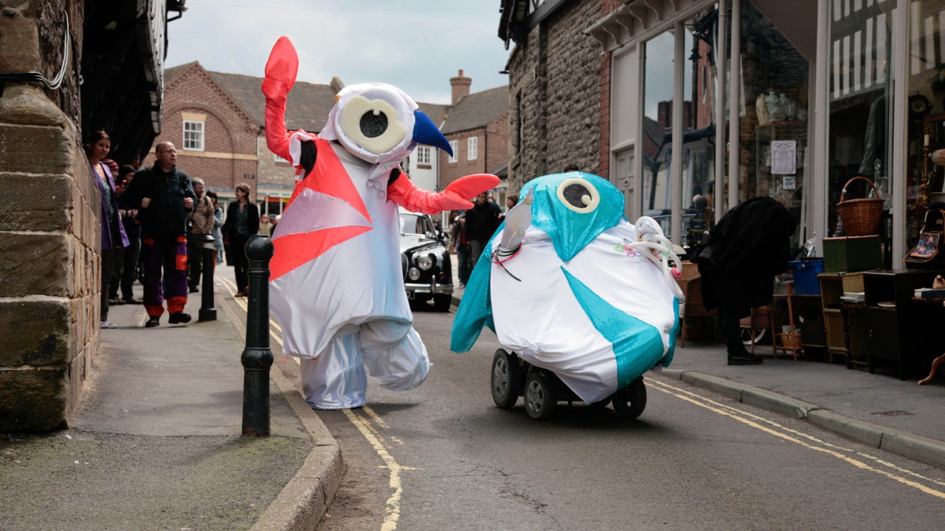 The artists are dressed as the cartoonish London Olympics mascots. They are moving through the streets.