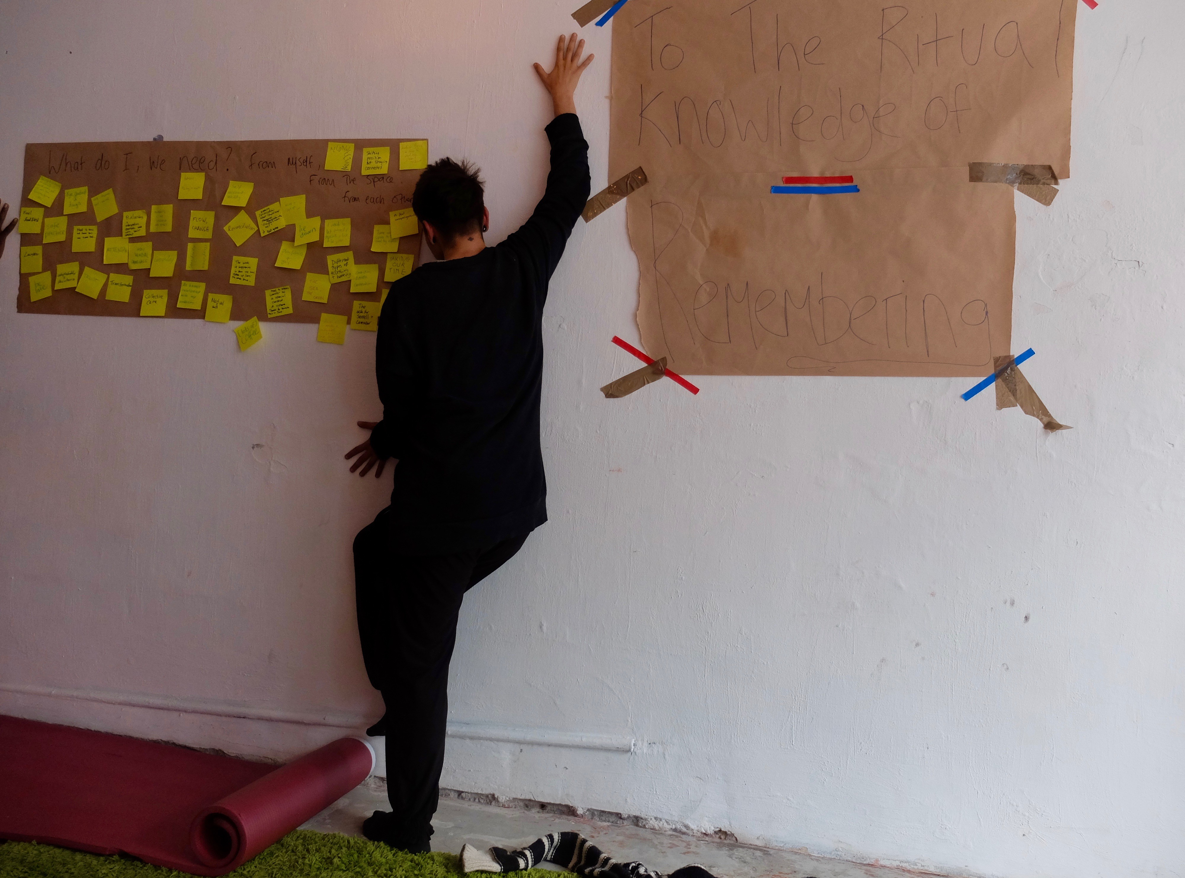 A workshop participant presses their body against a wall. Attached to the wall are various post it notes and paper sheets.