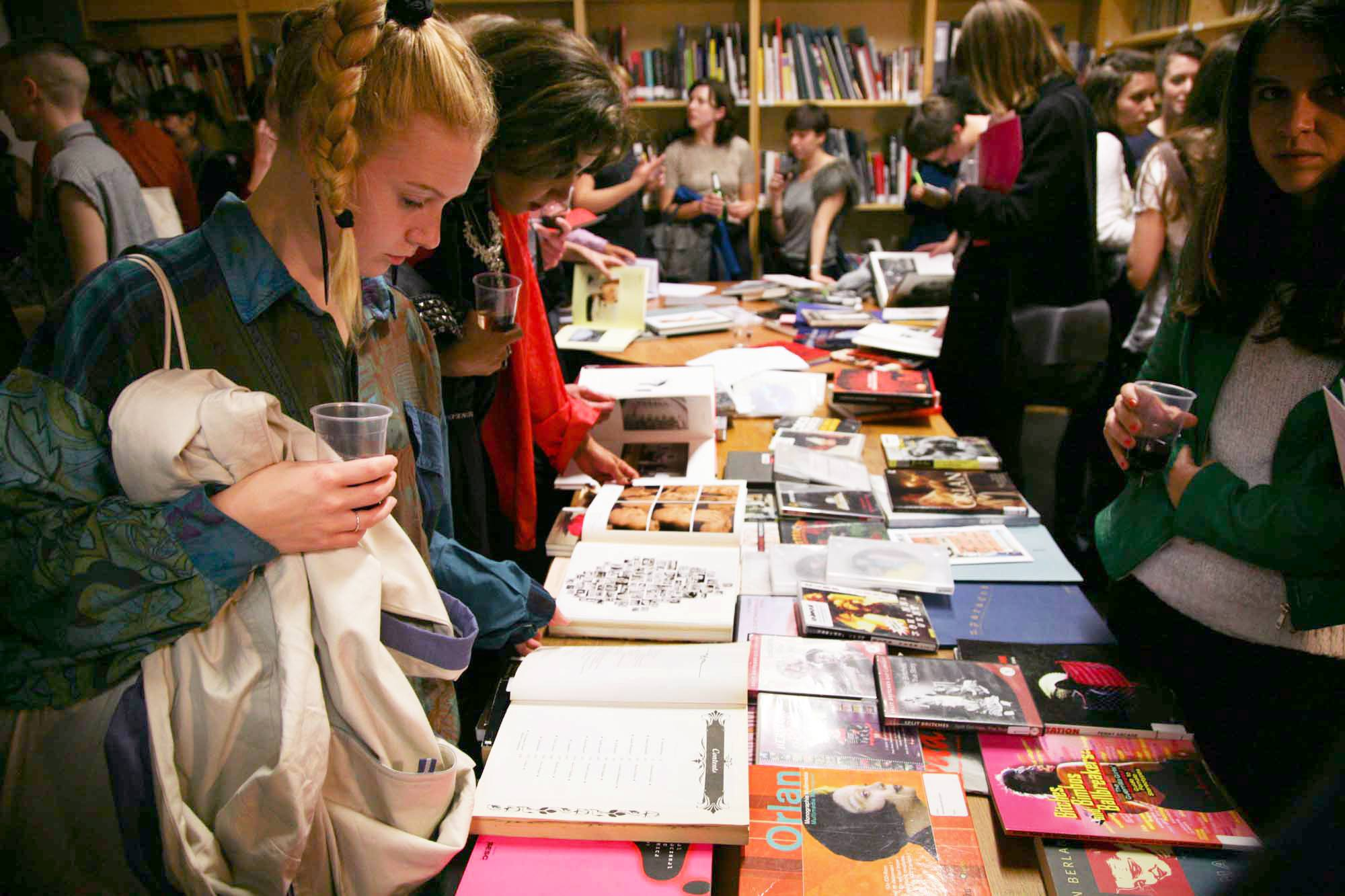 A group of Study Room users look at a table full of books in LADA's Study Room.