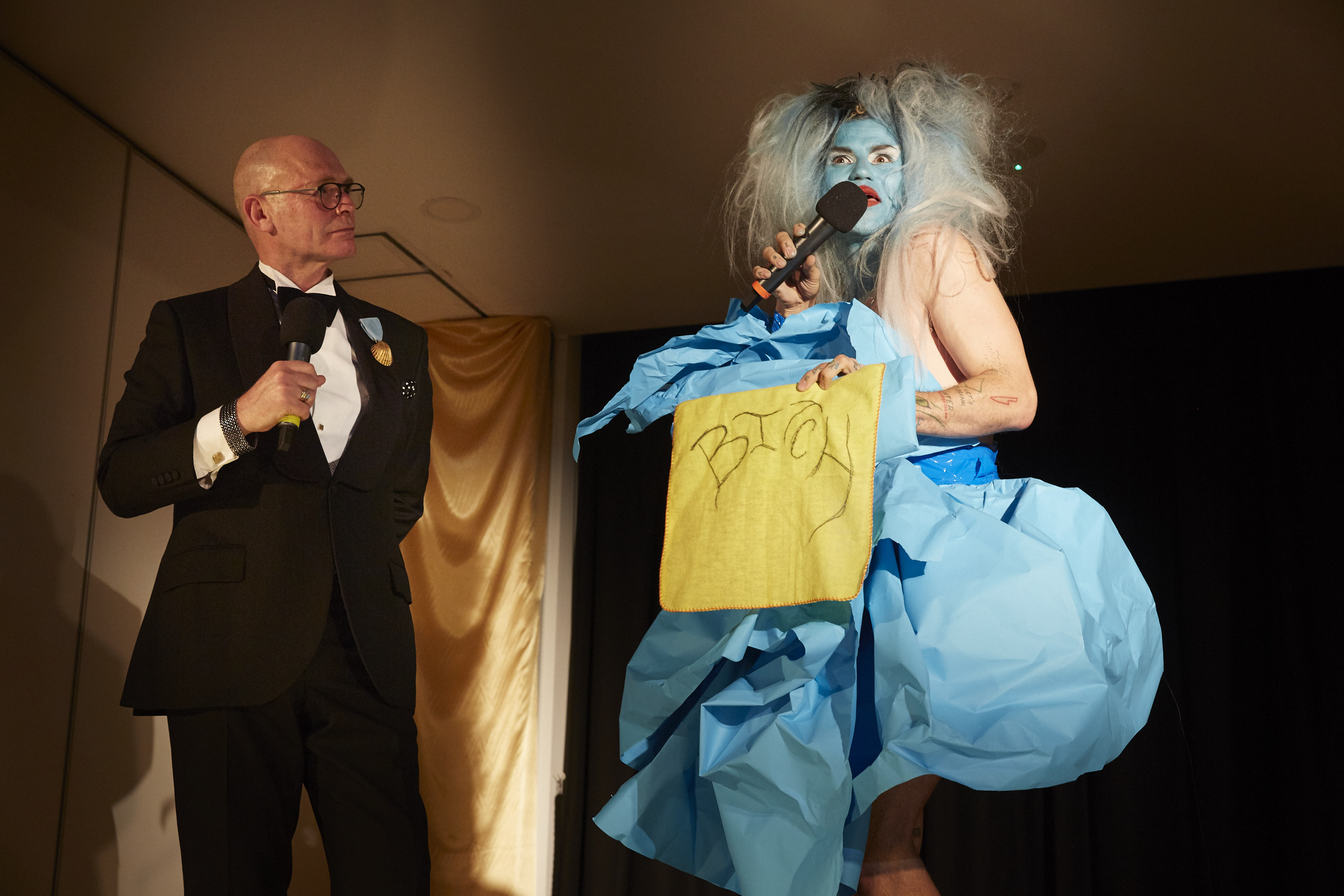 Drag performer with a blue face, wig and dress holds a yellow cloth with the word 'bitch' embroidered in it. An auctioneer in a tuxedo watches.