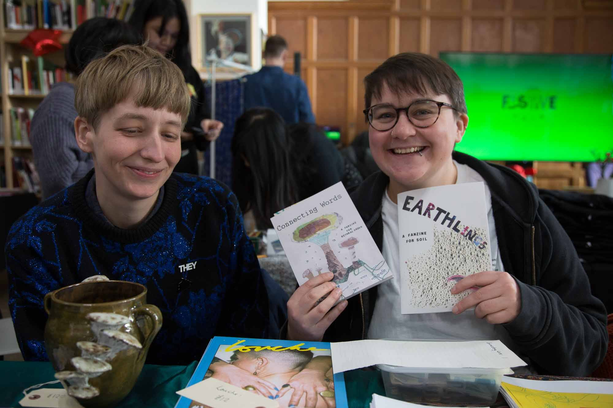 Two stall holders display their zines.