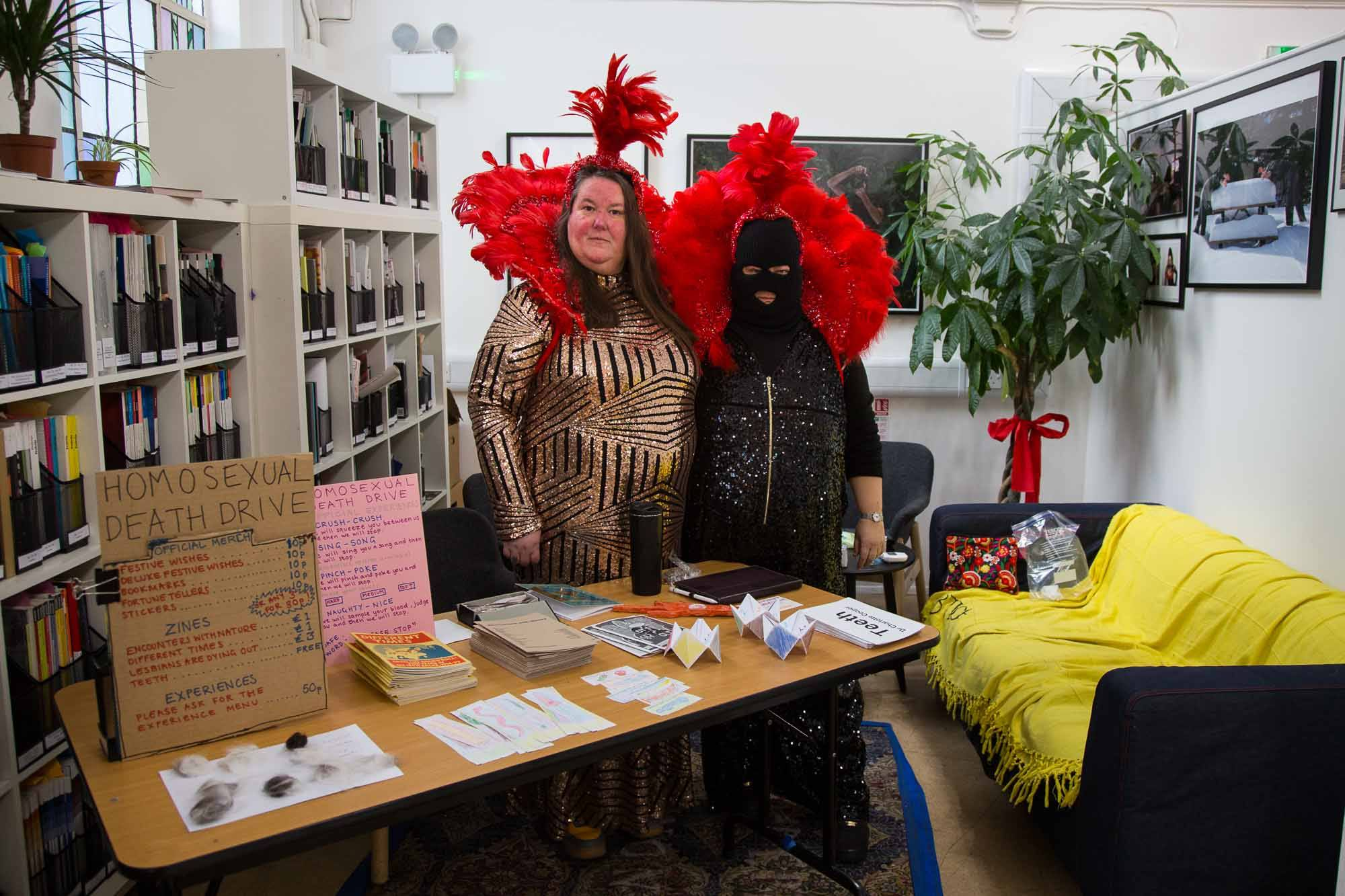 Homosexual Death Drive, a queer punk band stand behind a table of merch. They wear sparkly jumpsuits and red showgirl head pieces.