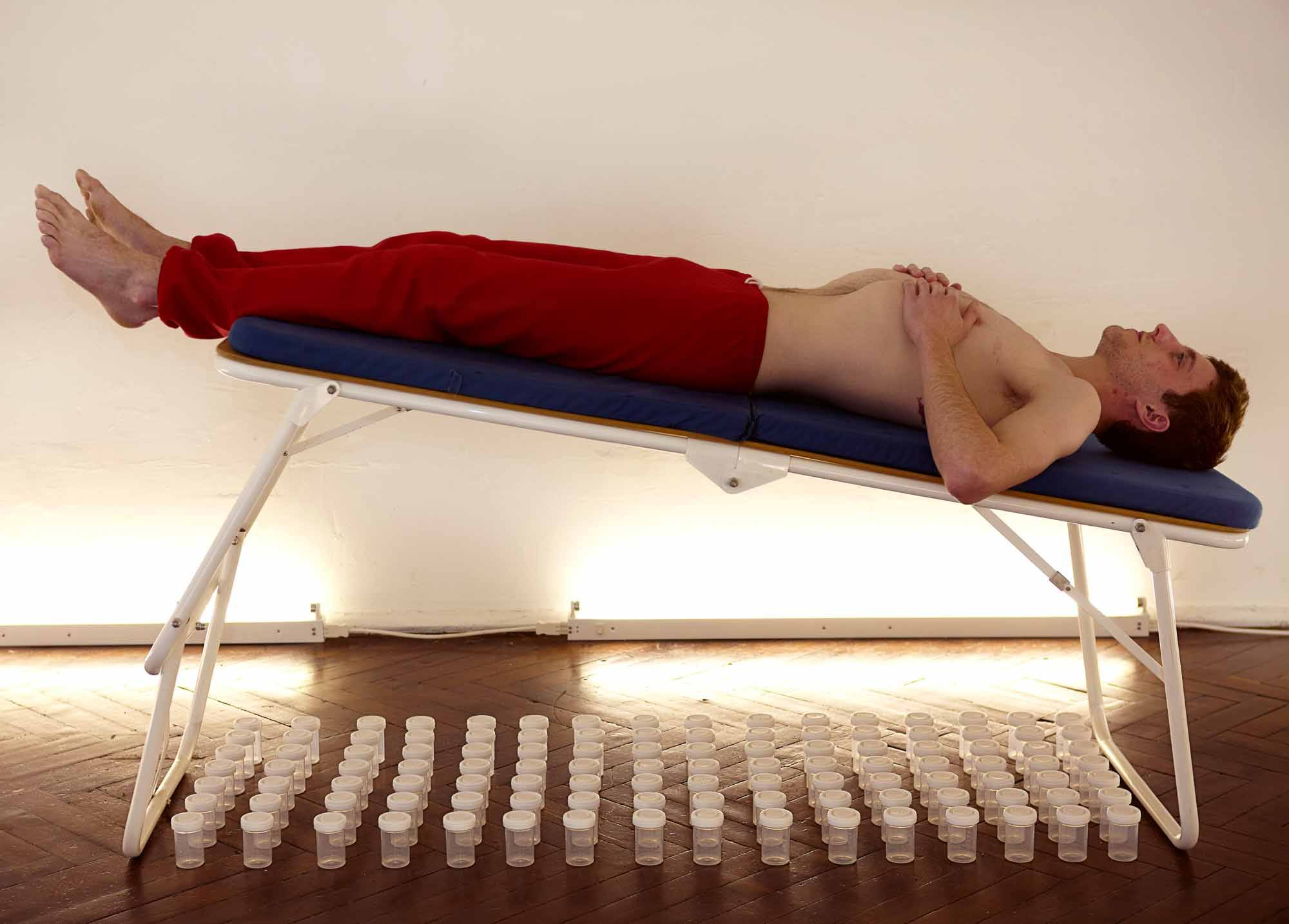 Martin lies on a bed above a large number of medical vessels. He beats his chest.
