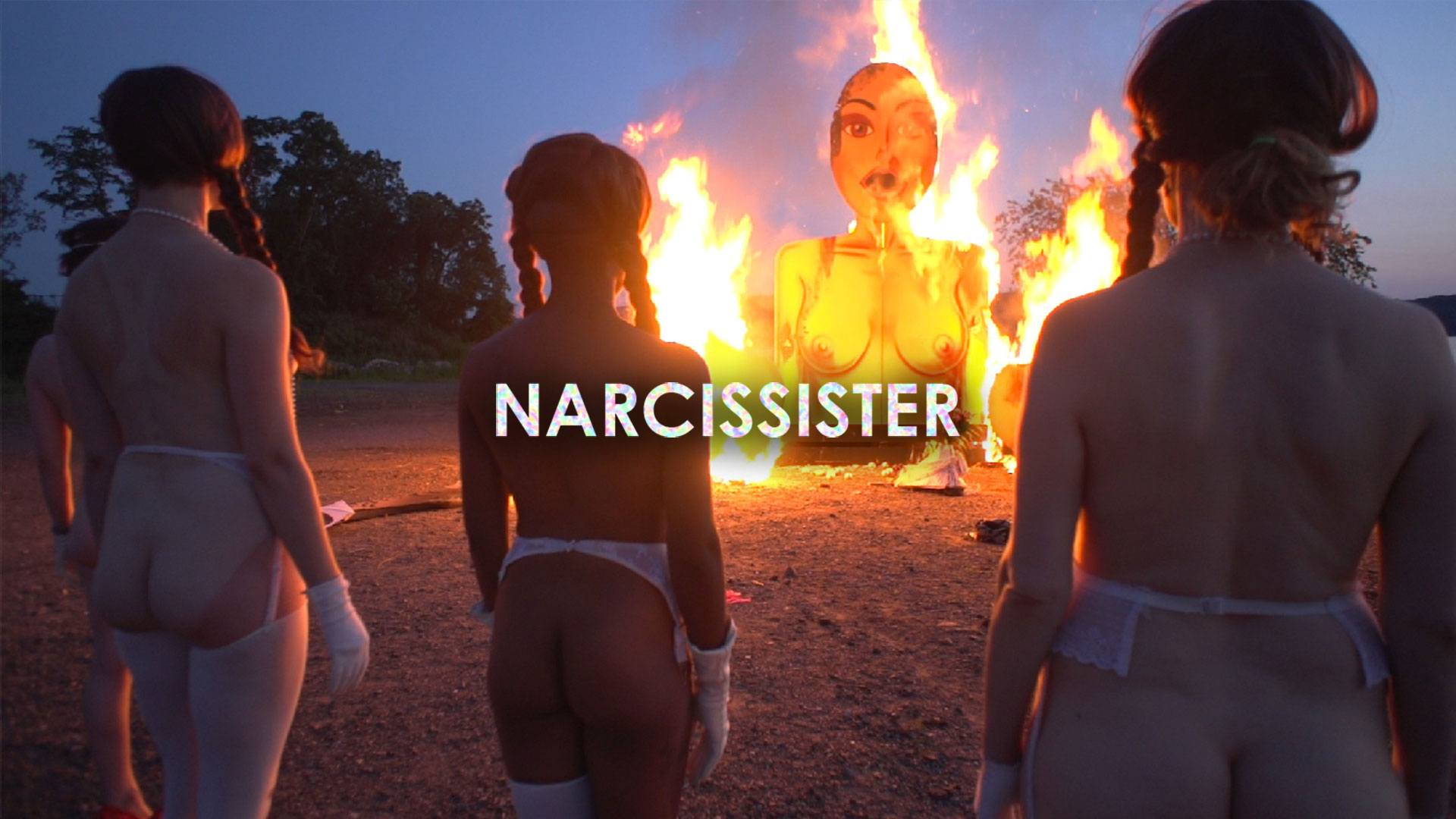 A group of women wearing masks stand round a giant burning effigy which resembles them.