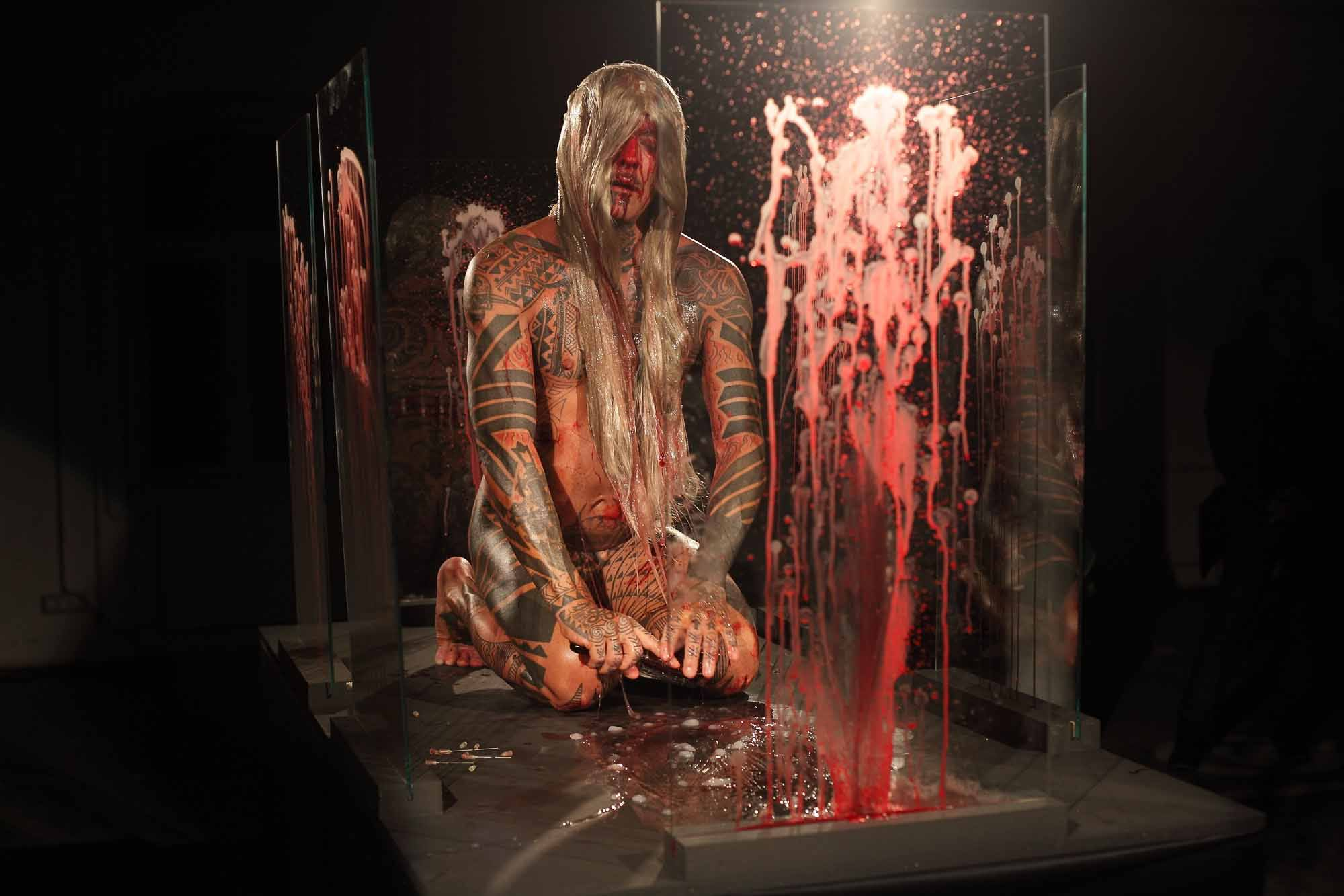 The artist is nude except for a blonde wig. He is surrounded by glass panes covered in his own blood.