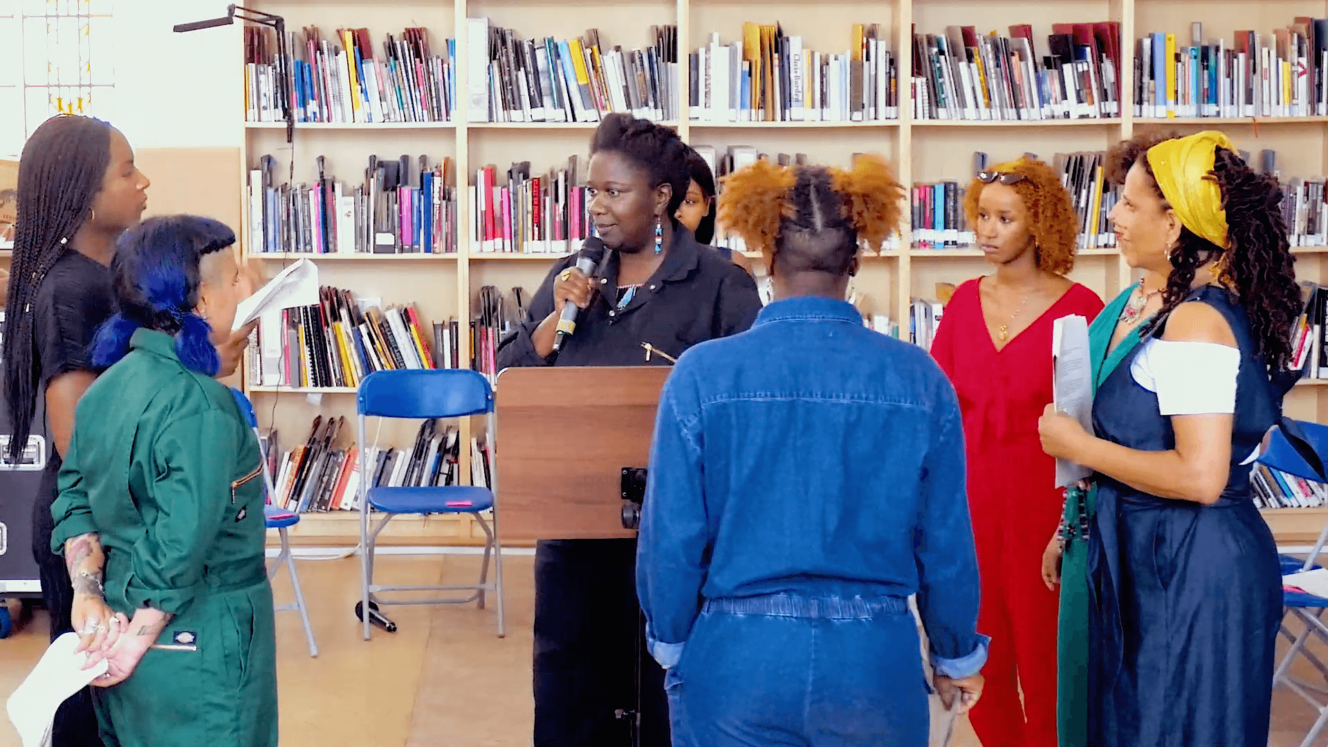 The artist speaks into a microphone surrounded by an intergenerational group of other women of colour.