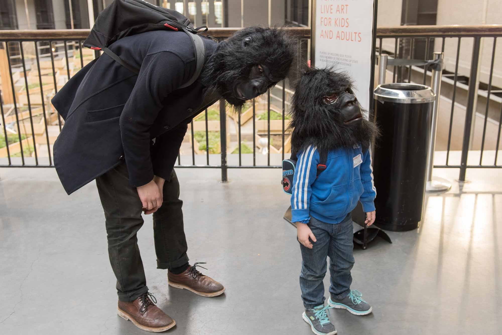 A young person and their parent wear gorilla masks in the Tate Modern Turbine Hall.