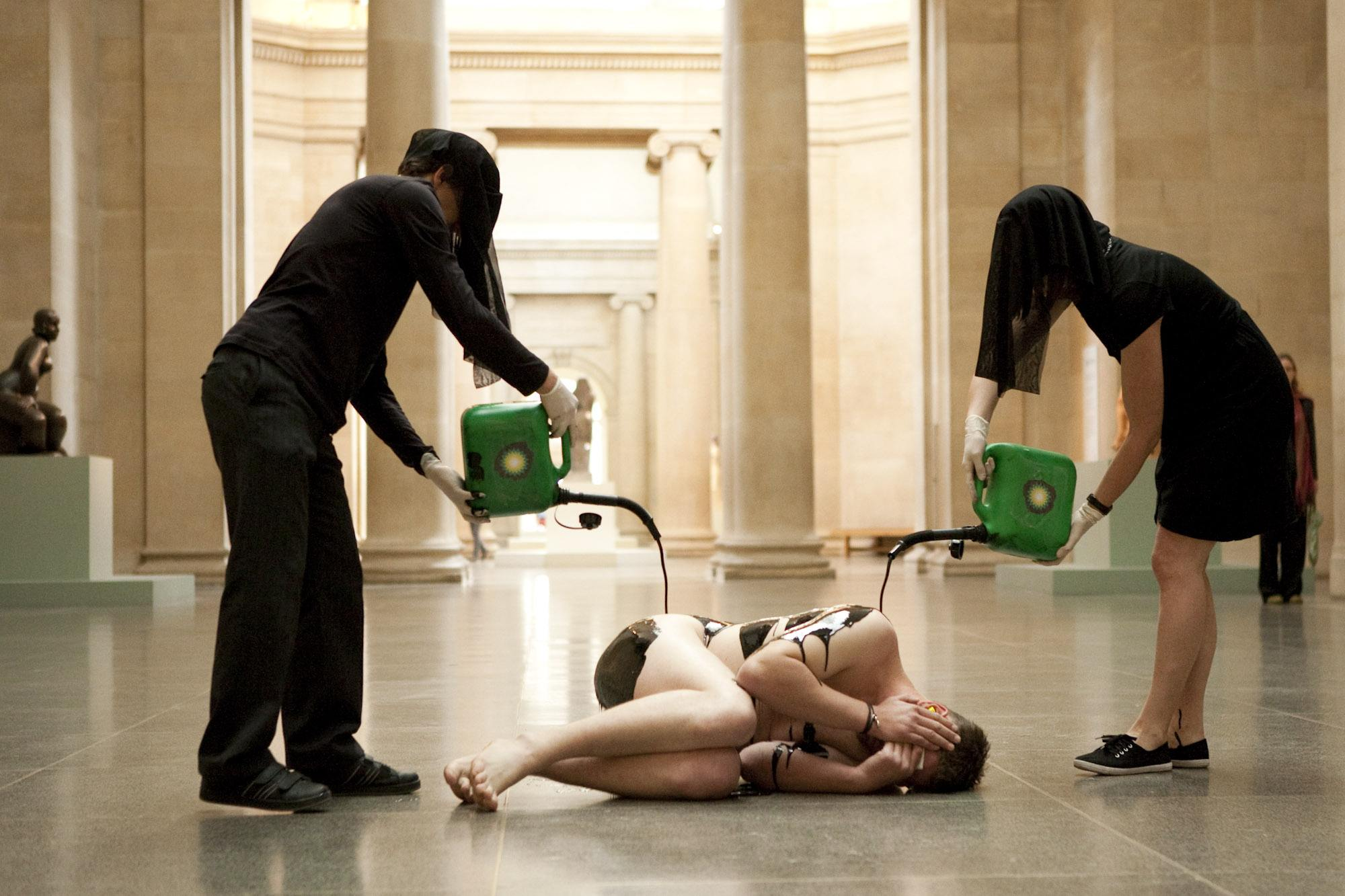 Two Liberate Tate activists pour a liquid resembling oil over a nude body in a gallery.