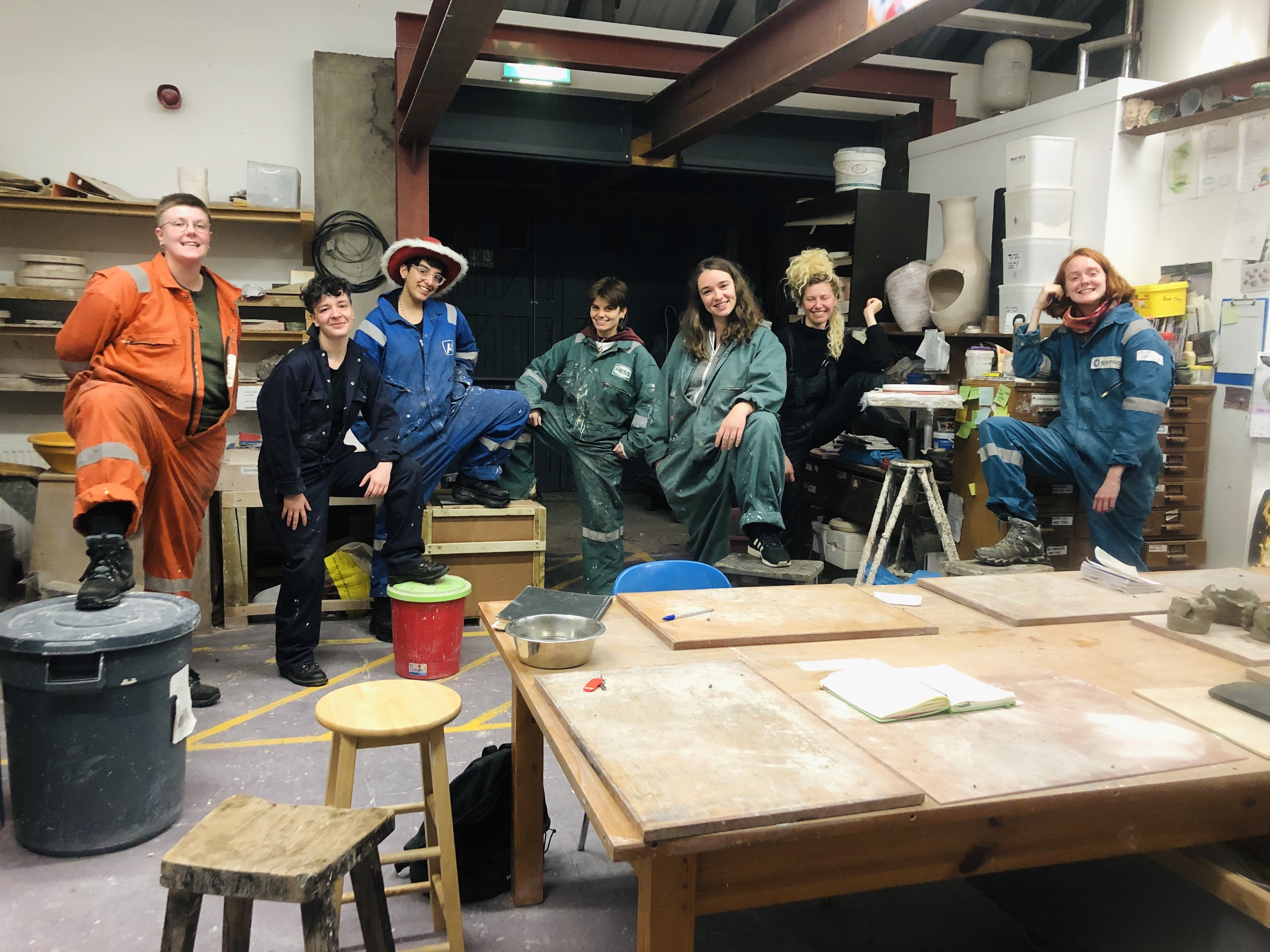 8 trans-masc artist pose in a clay/pottery studio in overalls, one person is wearing a red and white fluffy cowboy hat