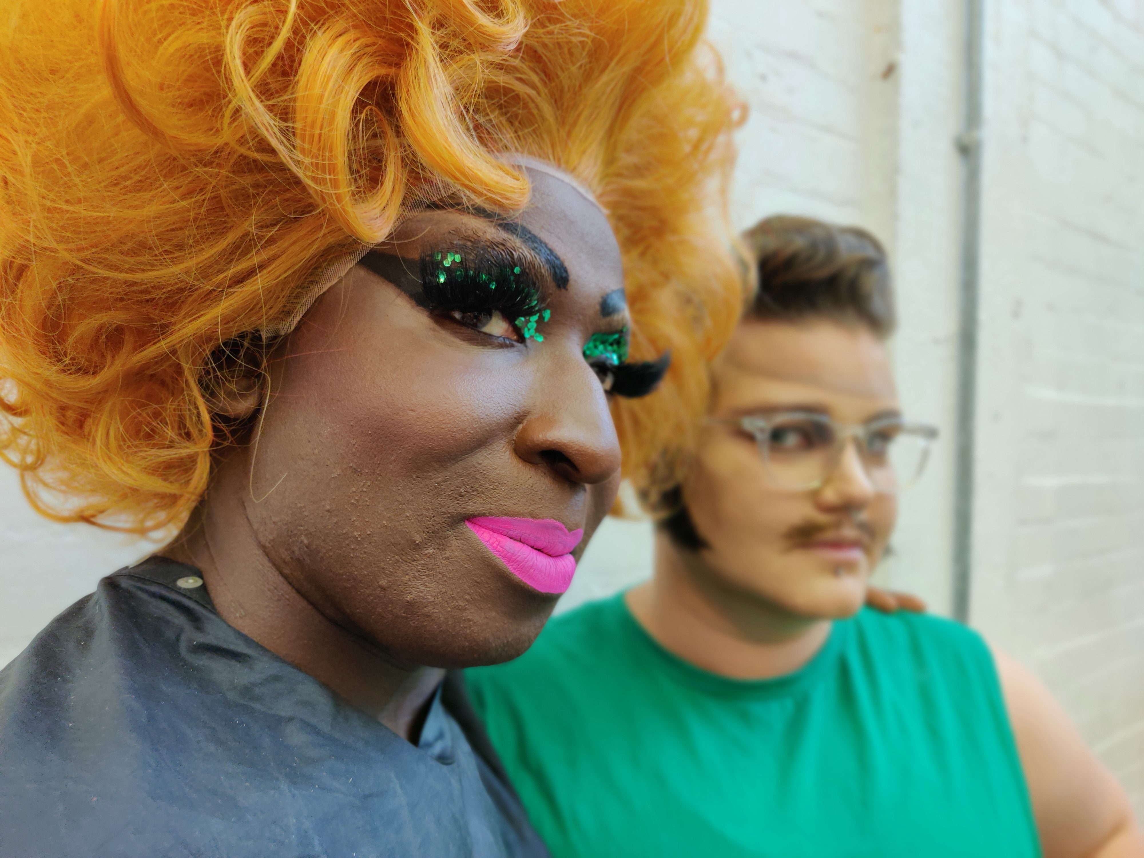 a close up image of a person in a large orange wig abd green glittery make up, with their arm around someone who is wearing a green t-shirt