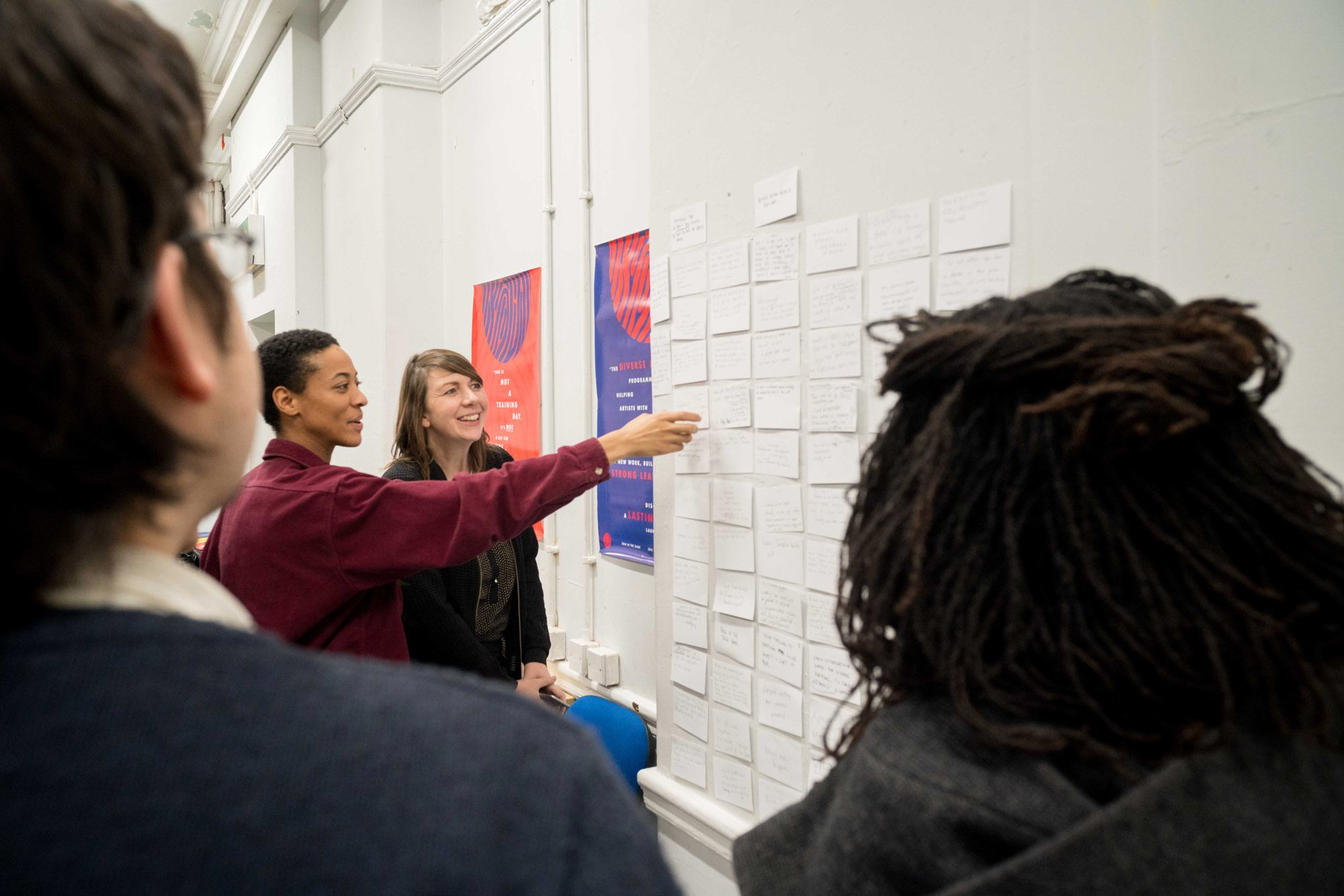 A group of participants look at notes on a wall.