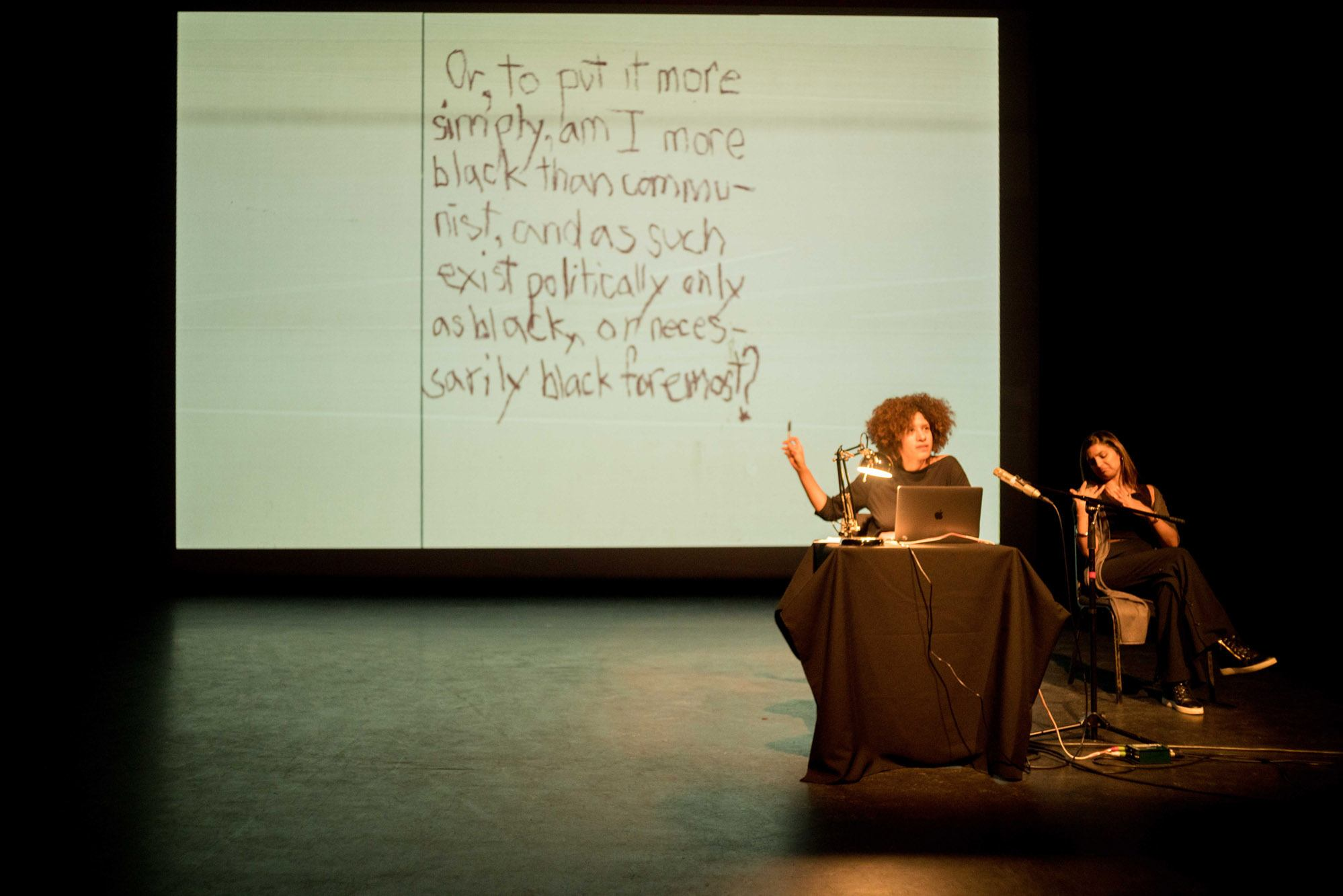 Performance: Season Butler (artist) sits at a table with a laptop and points to the projection screen behind her.