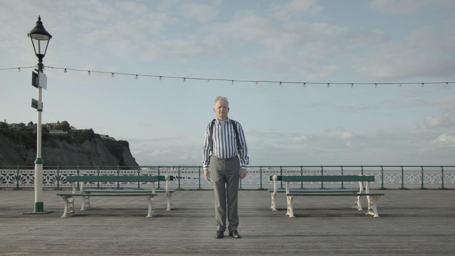 Tim Bromage is stood on a pier.