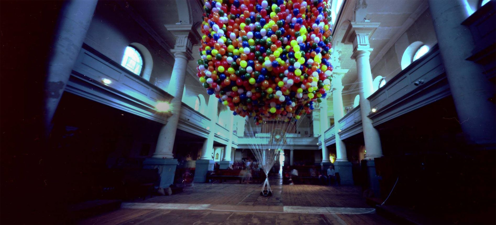 Artist is lifted into the air by hellium balloons