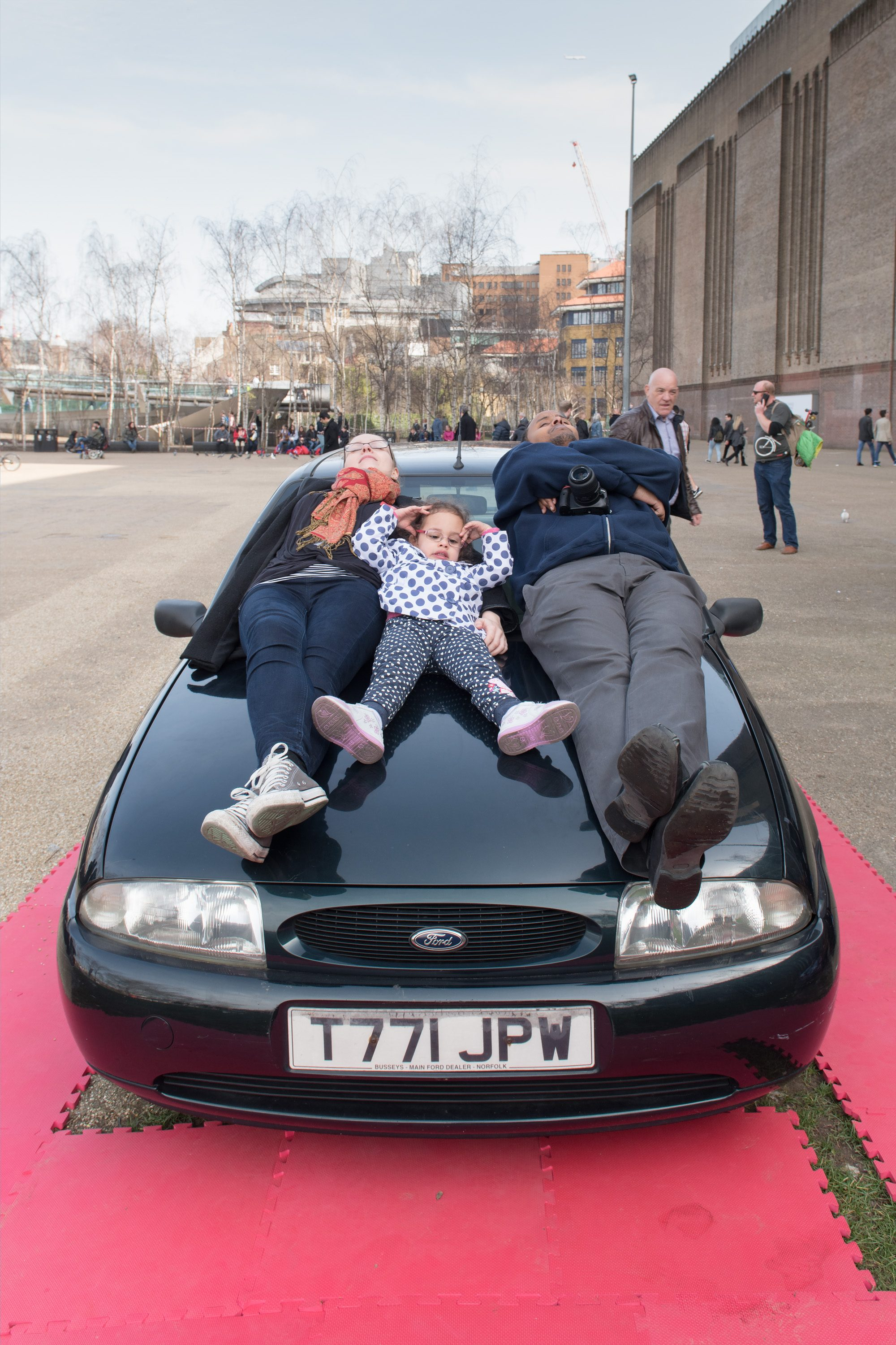 a child and two adults lie on top of a car outside the Tate Modern.