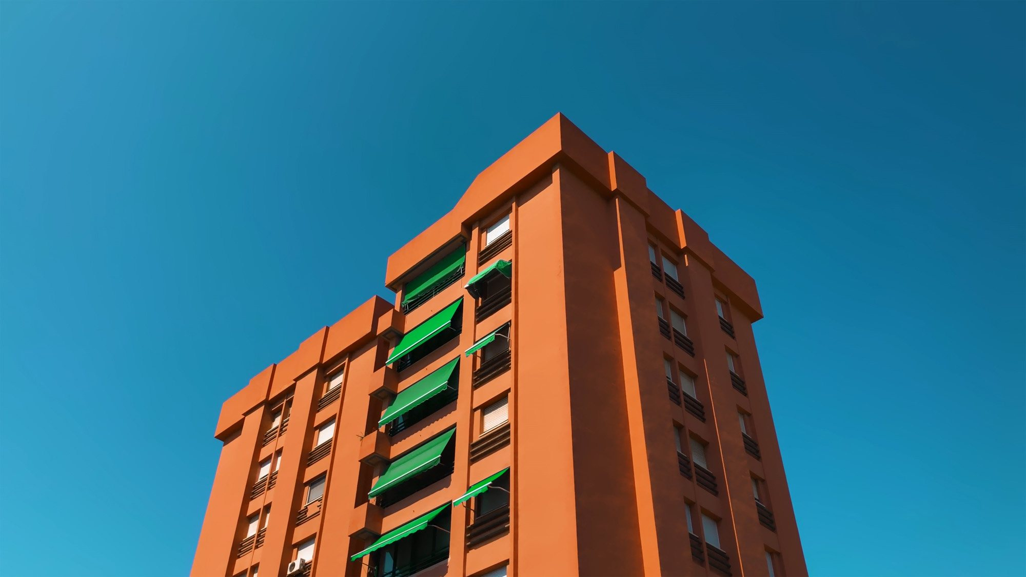 A orange tower block is shot from below, against a blue sky.