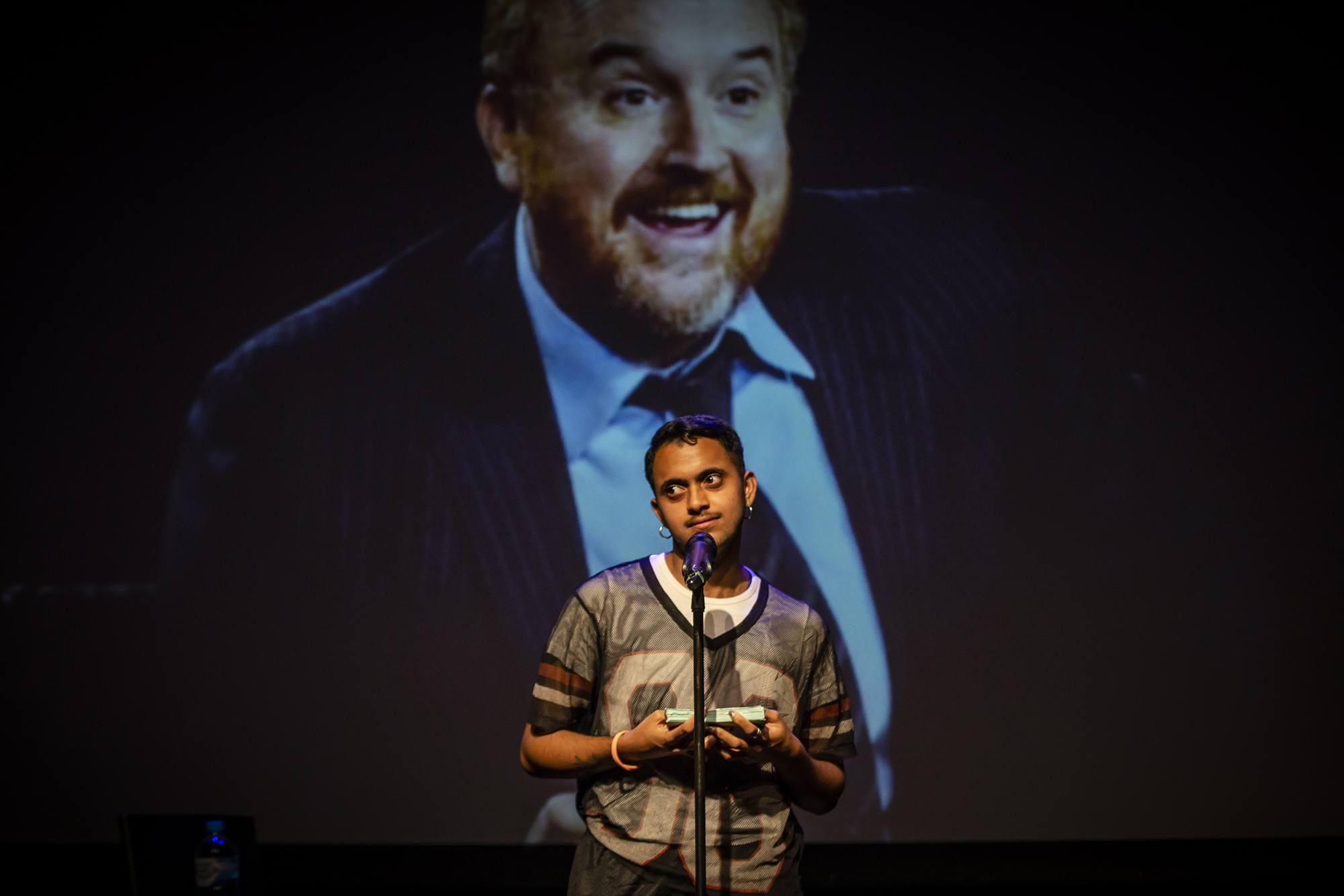 The artist speaks into a microphone as though doing a comedy set in front of an image of Louis CK.