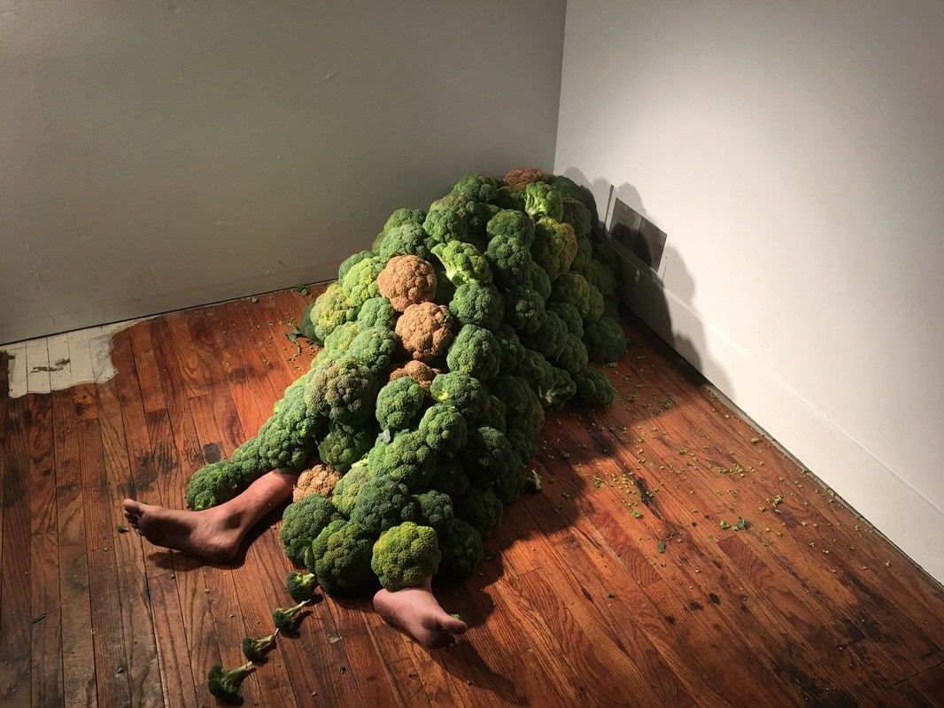 A body is covered by broccoli and lies prone on the floor.