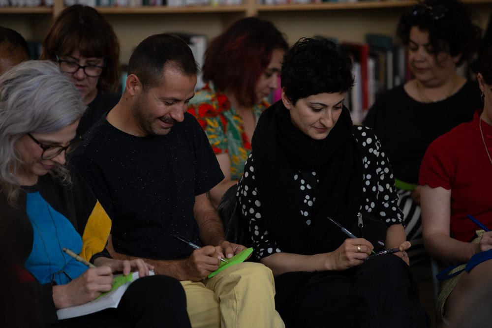 Several audience members write on post-it notes during the pbLIVE symposium.