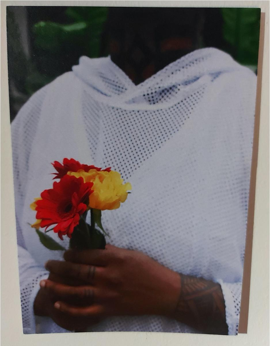 A close-up of a person in a white mesh hoodie holding flowers. They are a black person with a tattoo showing on their wrist and fingers.