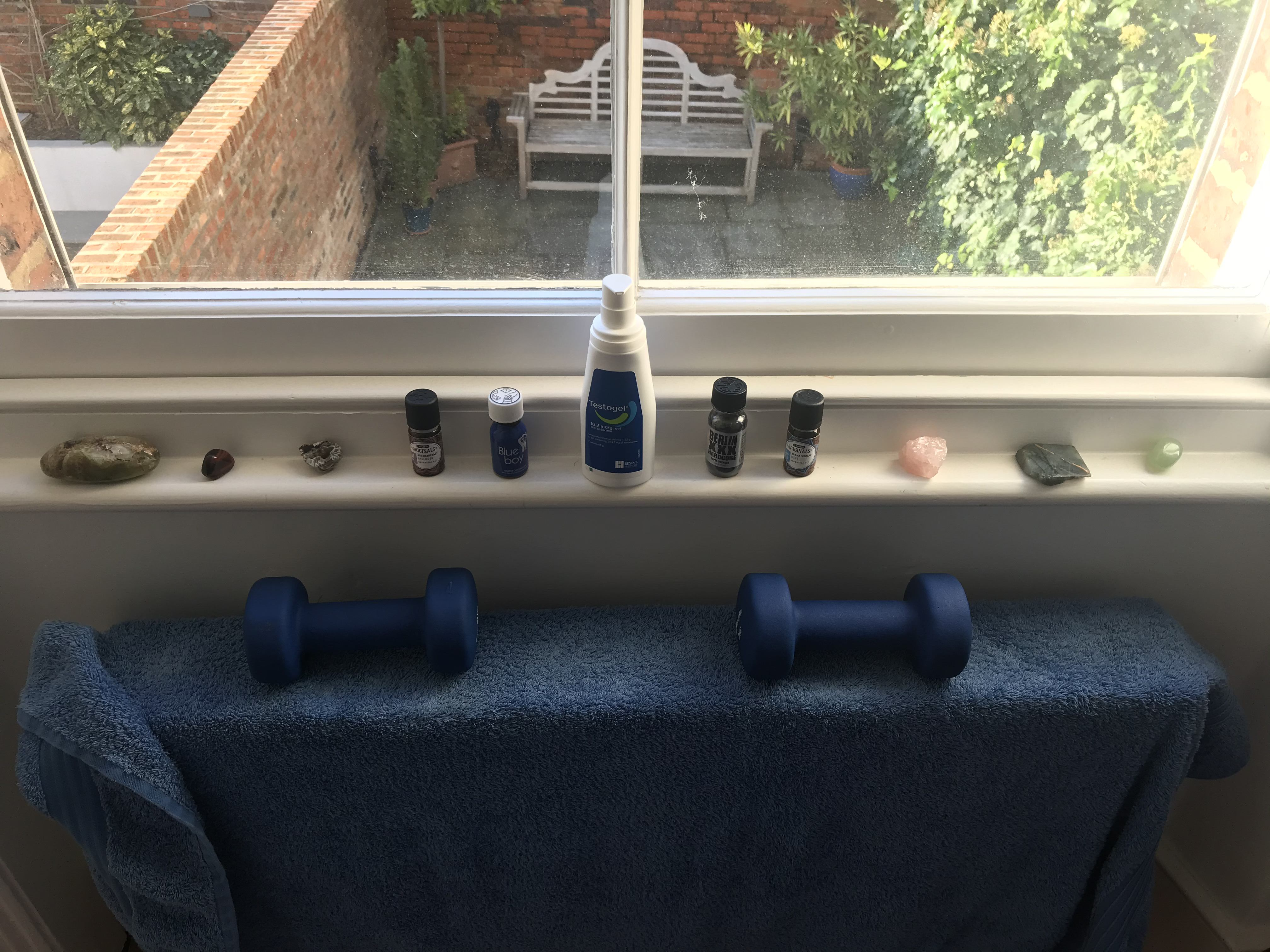 An alter: a bottle of testogel on a thin window ledge with either side of it various small bottles and crystals. Below is a blue towel on a radiator, weighted down by two blue free weights. The image is sunny, and out the window at the top you can see a terrace garden below with a wooden bench and some greenery.